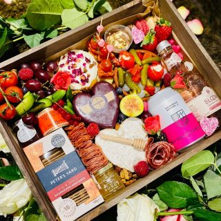 "Love is in the air...with our POSSE Valentine's Graze 💖 Our personalised wooden tray includes everything you need for a romantic graze. Our valentines inspired graze features three cheeses: a Neufchatel is a French heart shaped brie. This lovely heart cheese is believed to date back to the 6th Century, so a few Centuries younger than St Valentine himself. Legend has it that French farm girls fell in love with English soldiers during the Hundred Years War and started making heart shaped cheeses to show their love! A @godminster Cheddar Waxed Heart and a slice of Goats Cheese with edible rose petals. We have included @petersyard crackers, @comtesse_du_barry pate, @matersandco Cambridgeshire honey and drizzle stick, chutney, selection of charcuterie meats, pork pie, fresh fruits and vegetables, nuts, olives and pickles. We have included drinks from @brumbrewery and @bloomgin , these can be customised to include red, white or Prosecco just ask! We have also included a few treats: macrons, chocolate ganache, heart chocolates and heart shaped jelly beans. Our personalised ""Valentines POSSE"" is £70 #grazingtables #grazingtable #grazingtablesandcheeseboards #grazing #grazingplatter #grazingboard #grazingbox #solihullbusiness #solihull #solihullfood #solihullfoodie #birminghambusiness #birminghamfood #birminghamfoodie #foodtrends #spreadsandbreads #foodporn #platters #partyfood #eventcatering #foodevents #foodgifts #valentines #valentinesgift #valentines2021 #spreadsandbreadssolihull #weddingcatering #weddingcaterer #partycatering #partycaterer @solihullcouncil @solihullforsuccess @mousetrapcheese"
