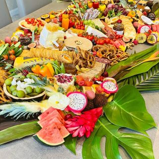 """all hail…the tropical grazing table 🌺🌴🍍🍉🥥  It feels so good to be back creating grazing tables today, we created a tropical inspired """"Flat Lay Graze"""" straight on to the birthday girls table.  The client sent us a cheese leaf plant tropical napkin for inspiration, for his wife's birthday celebrations.  This table is a one metre savoury graze which feeds 30 adults with add on desserts. So a metre and half of quality produce ready for the party guests to start grazing!!!  Make a statement at your next event, whether the occasion is big or small, trust Spreads and Breads to create that show-stopping display of food that promises to amaze your guests, creating a fantastic atmosphere whether its an intimate gathering, a girls night in or a big celebration for a special birthday, wedding or product launch.  Classic Flat Lay - straight on to table or surface - £12 per grazing head. Or for Children £8 per grazing child. Add desserts for +£3 per grazing head   Our tables start from 1 METRE which is based on 30 people!   #grazingtables #grazingtable #grazingtablesandcheeseboards #grazing #grazingplatter #grazingboard #grazingbox #solihullbusiness #solihull #solihullfood #solihullfoodie #birminghambusiness #birminghamfood #birminghamfoodie #foodtrends #spreadsandbreads #foodporn #platters #partyfood #eventcatering #foodevents #foodgifts  #spreadsandbreadssolihull  #weddingcatering #weddingcaterer #partycatering #partycaterer @solihullcouncil @solihullforsuccess"""