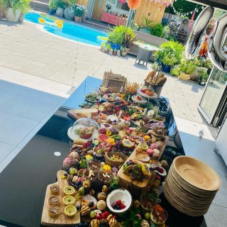 Pool Party Grazing 💦 ☀️  On one of the hottest days of the year we created a metre and a half of layered table graze with savoury and desserts for a 60th Birthday celebration this afternoon.   We covered and left ice packs with today's customer to keep it all cool until the party started 🧊🧊🧊  At Spreads and Breads we like to keep life simple, that's why we have two price options:  Classic Flat Lay - straight on to table or surface - £12 per grazing head. Or for Children £8 per grazing child. Add desserts for +£3 per grazing head   Layered Styled Package - using our props (glass domes, wooden boards, bowls etc) with flowers and foliage - starting from £60  Our tables start from 1 METRE which is based on 30 people! We use flowers and foliage to adorn each adult display but if you have something extra special in mind let us know! Arrangements will be made to collect the serve ware the same or the following day - collection fee applies £30+travel.   Please note it takes between 90-180 minutes on average to create the grazing tables in your venue. So we will require access to the venue 2+ hours before your event begins.  We are more than happy to work with you to make your table as bespoke as you like, so if there is something, you'd specifically like to include we will do our best to source this for you. Likewise, if there are some things you'd rather not include on the table, we simply remove it and replace with something else!!  We can also add wooden palm leaf, biodegradable cutlery and plates if you would like us too, these are optional extras and will be an additional cost but make the table look amazing!! Palm leaf table wear and cutlery can be provided for a cost of £1.20 per head.  #grazingtables #grazingtable #grazingtablesandcheeseboards #grazing #grazingplatter #grazingboard #grazingbox #solihullbusiness #solihull #solihullfood #solihullfoodie #birminghambusiness #birminghamfood #birminghamfoodie #foodtrends #spreadsandbreads #foodporn #platters #partyfood #e